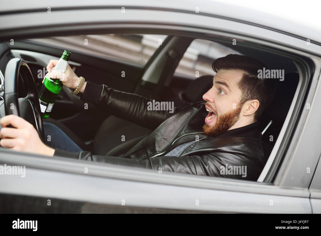 Drunk man with a bottle of beer driving a car - Stock Image
