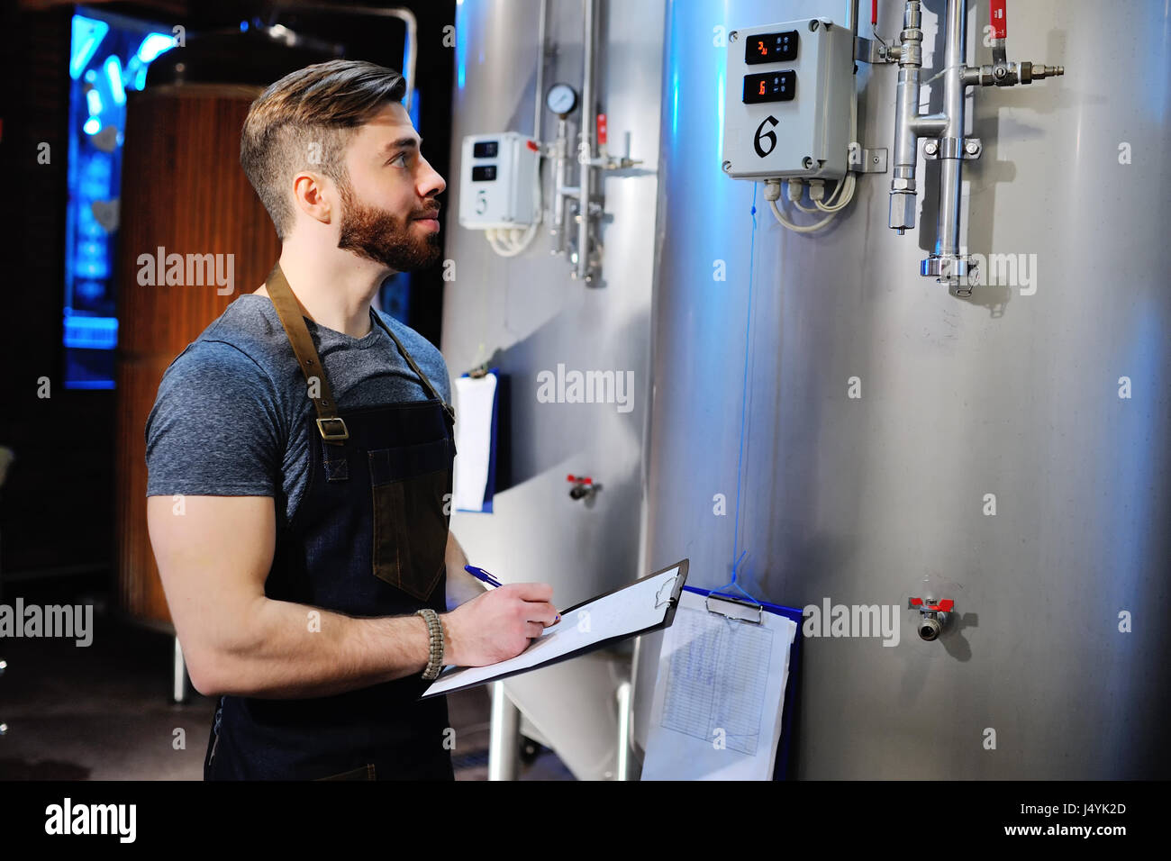 A handsome bearded male brewer records data against a background of beer tanks. Brewing - Stock Image