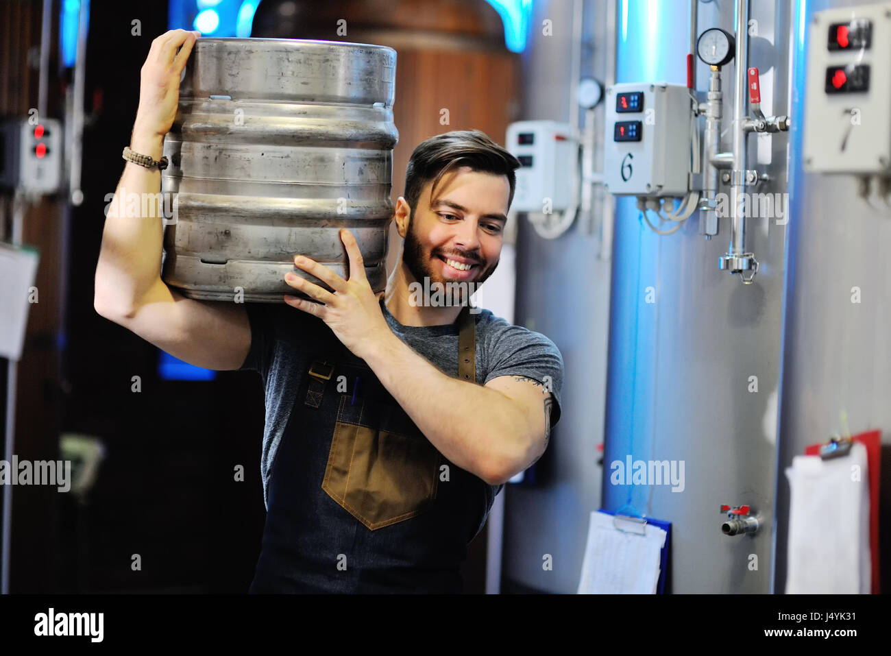Man with a beard working in uniform with a barrel of beer in a brewery with metal containers in the background Stock Photo