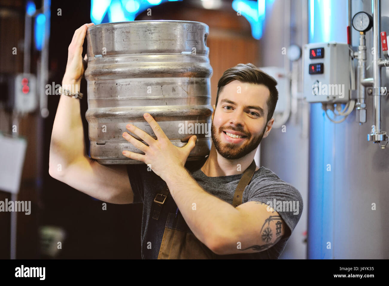 Male brewer with a metal beer barrel on the background of the brewery Stock Photo