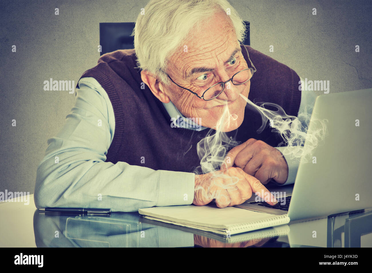 Stressed elderly man using computer blowing steam from nose frustrated sitting at table isolated on gray wall background. - Stock Image
