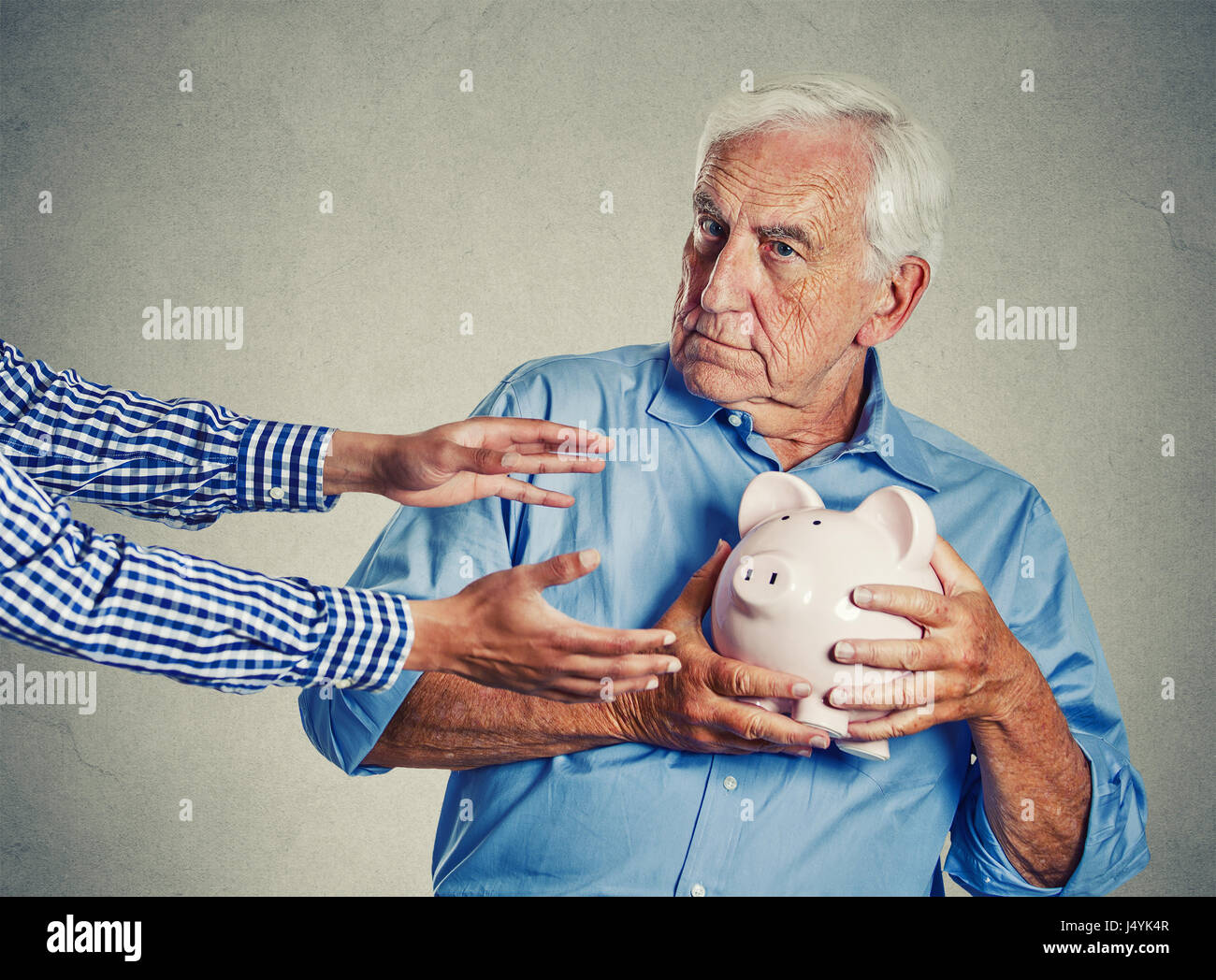 Closeup portrait senior man grandfather holding piggy bank looking suspicious trying to protect his savings from - Stock Image