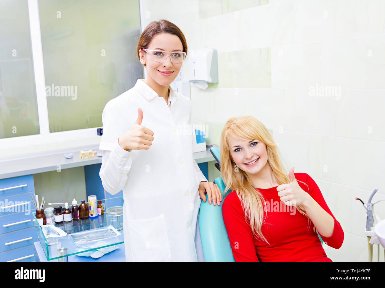 Closeup portrait happy female health care professional dentist, satisfied smiling woman patient in office giving - Stock Image