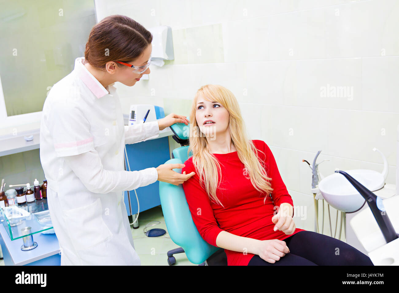 Closeup portrait sad girl, patient woman with painful tooth, ache siting in chair, medical office explaining her - Stock Image