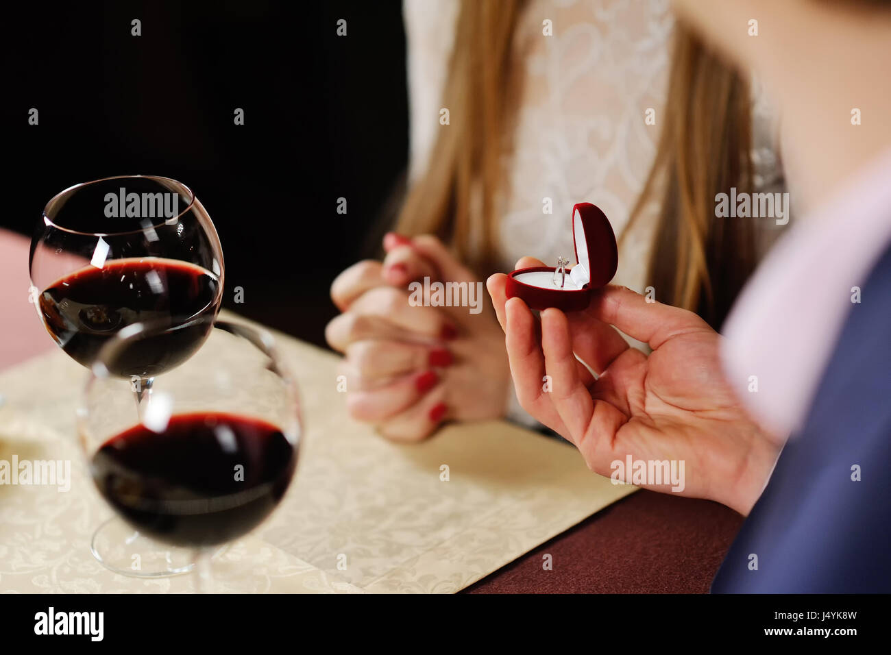 guy doing the girl proposal in restaurant. man gives a woman an  - Stock Image