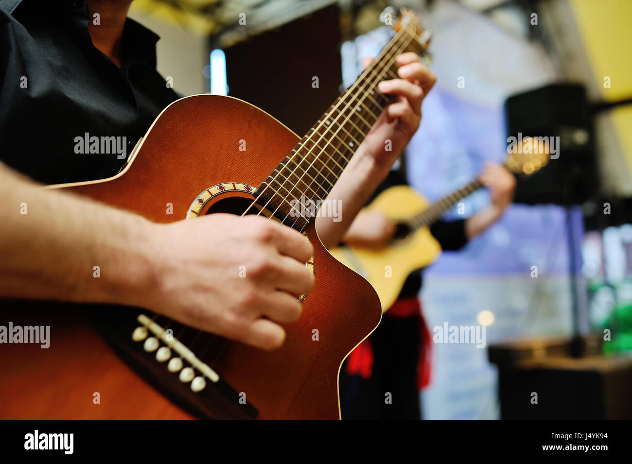 two musicians playing guitars - Stock Image