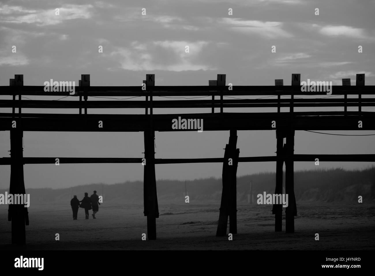 People Walking on the Beach by a Pier, Black and White - Stock Image