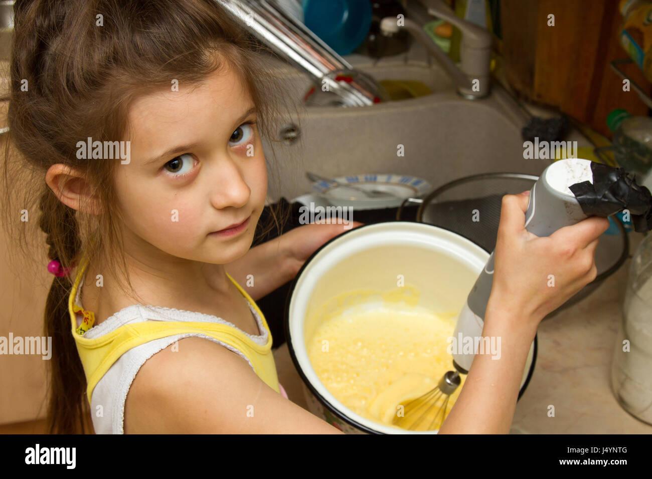 Child preparing cookies in kitchen. - Stock Image