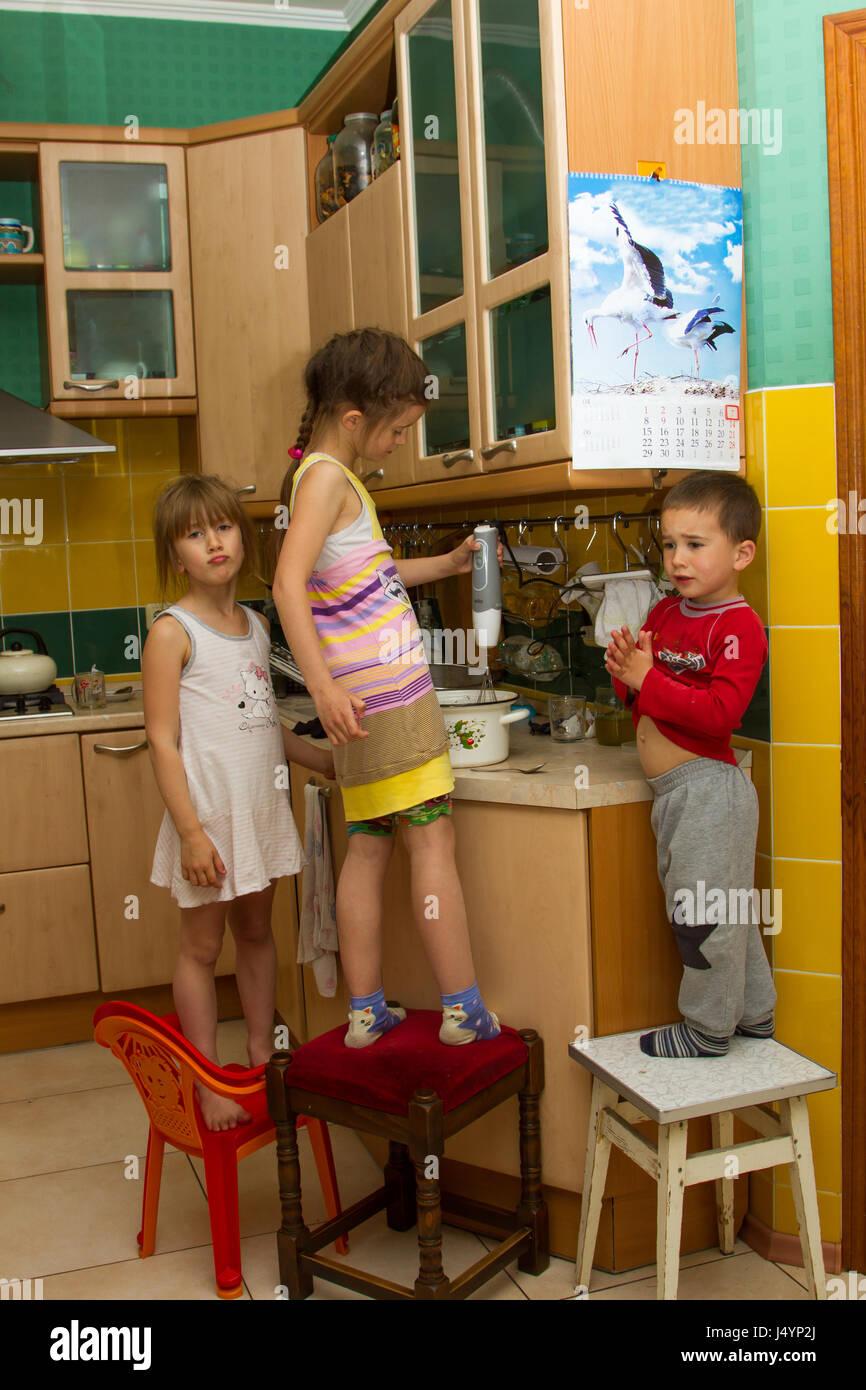 Three children in the kitchen - Stock Image