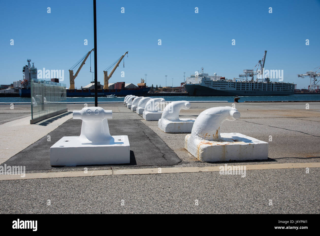 White moorings on the waterfront dock with commercial dock view, nautical vessels and large cranes on a clear day - Stock Image