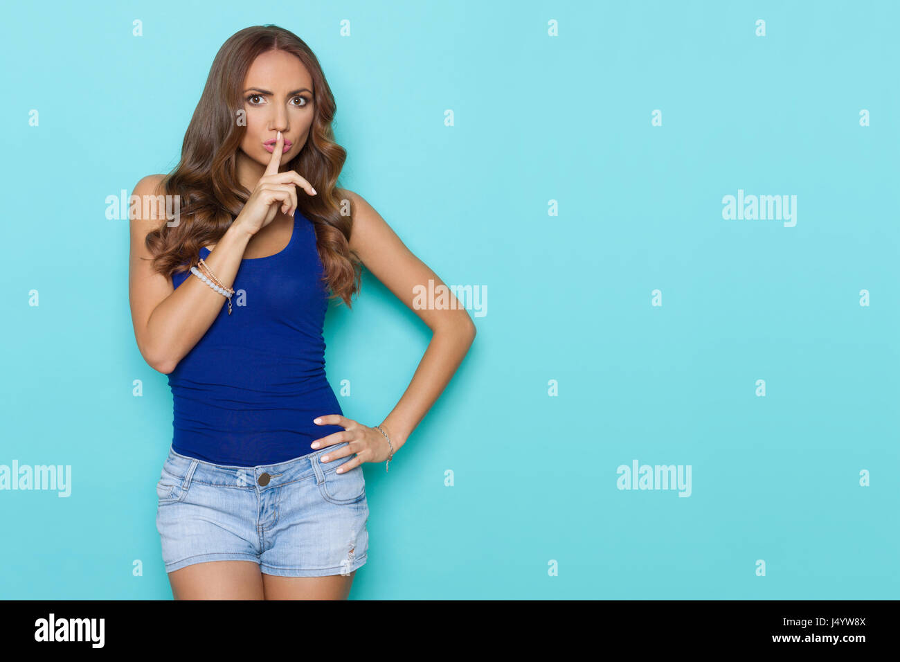 Young woman in blue shirt and jeans shorts is holding finger on lips and looking at camera. Three quarter length - Stock Image