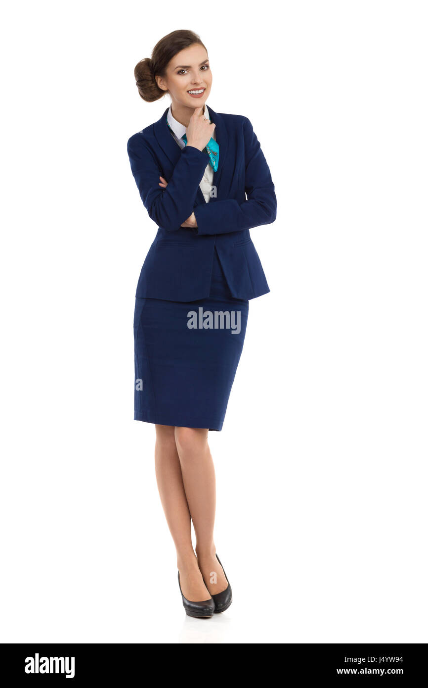 Young businesswoman in blue formalwear and high heels is smiling and looking at camera. Front view. Full length - Stock Image