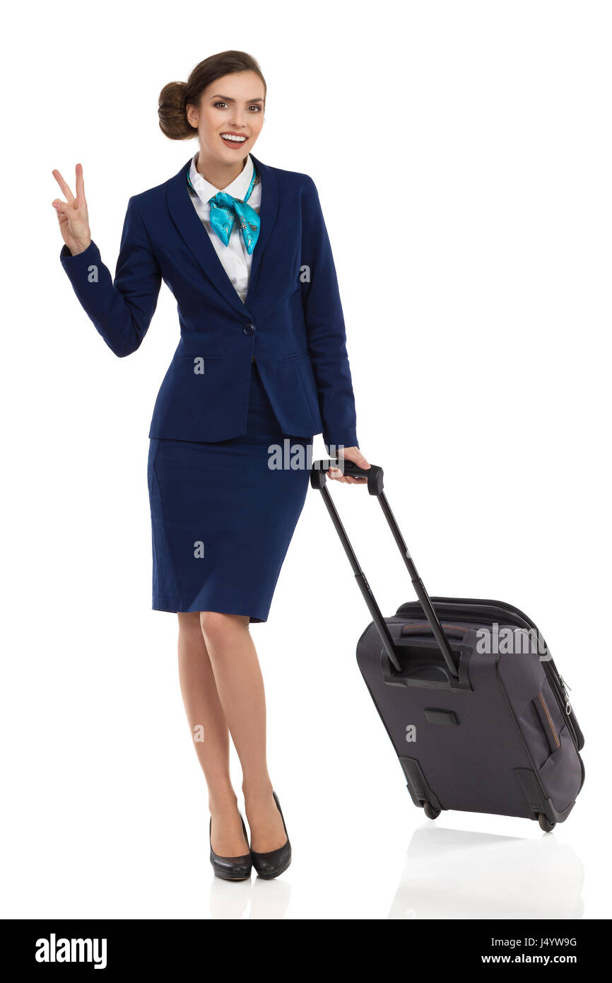 Smiling businesswoman in blue formal wear is standing with trolley bag, showing peace sign and looking at camera. - Stock Image