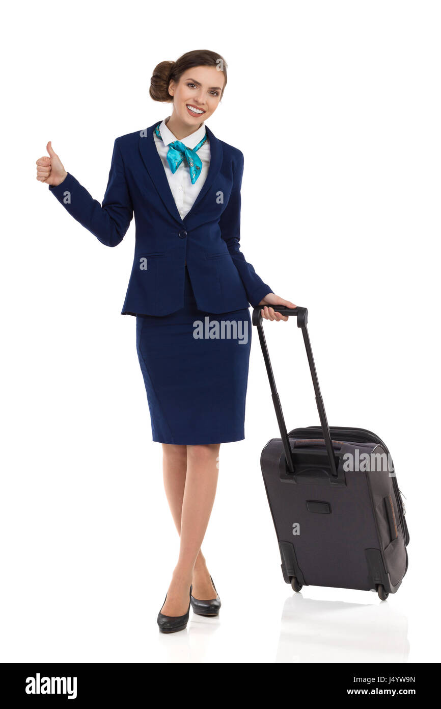 Smiling stewardess woman in blue suit and skirt is standing with trolley cabin baggage, showing thumb up and looking - Stock Image