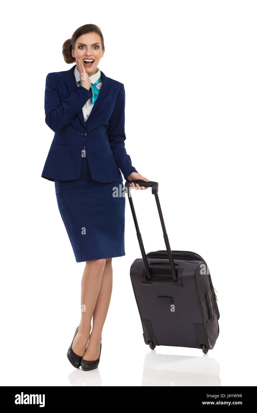 Excited businesswoman in blue suit and skirt is standing with trolley bag, holding hand on chin and looking at camera. - Stock Image