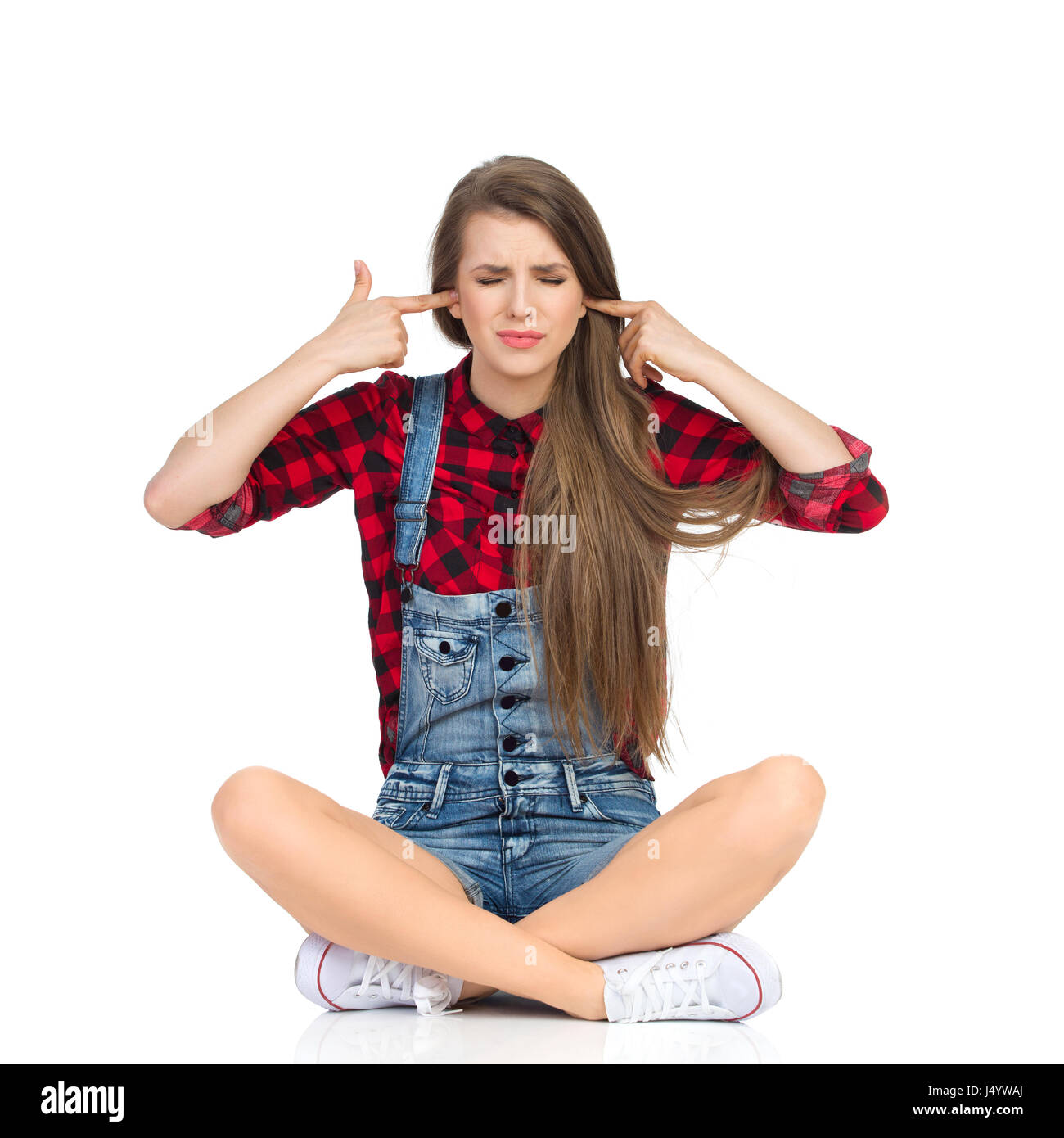 Disgusted young woman in red lumberjack shirt, jeans shorts and white sneakers sitting on a floor with legs crossed, - Stock Image