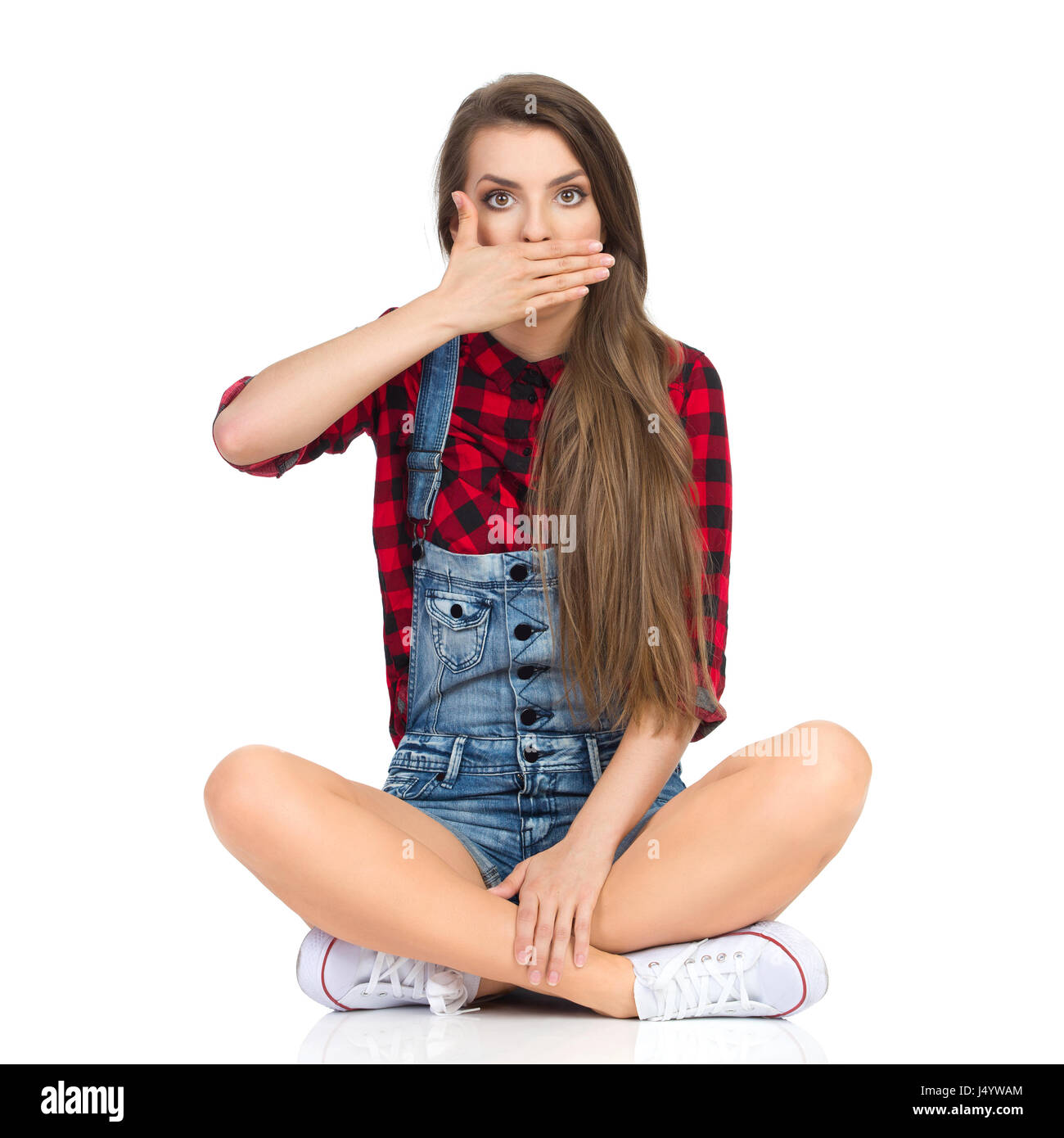 Young woman in red lumberjack shirt, jeans shorts and white sneakers sitting on a floor with legs crossed and holding - Stock Image
