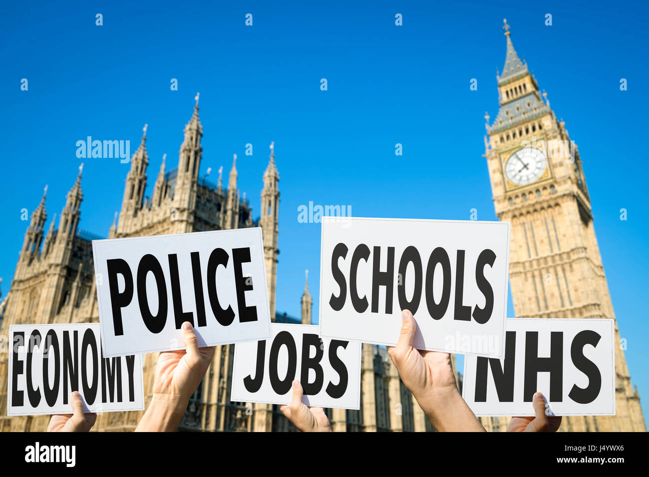 Hands holding signs with election issues like economy, police, jobs, schools, and the NHS outside Houses of Parliament - Stock Image