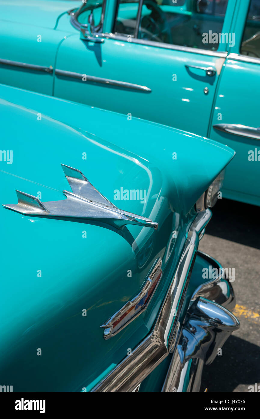 HAVANA - CIRCA JUNE, 2011: The hood ornament of 1953 Chevrolet BelAir gleams in the tropical sun next to another - Stock Image