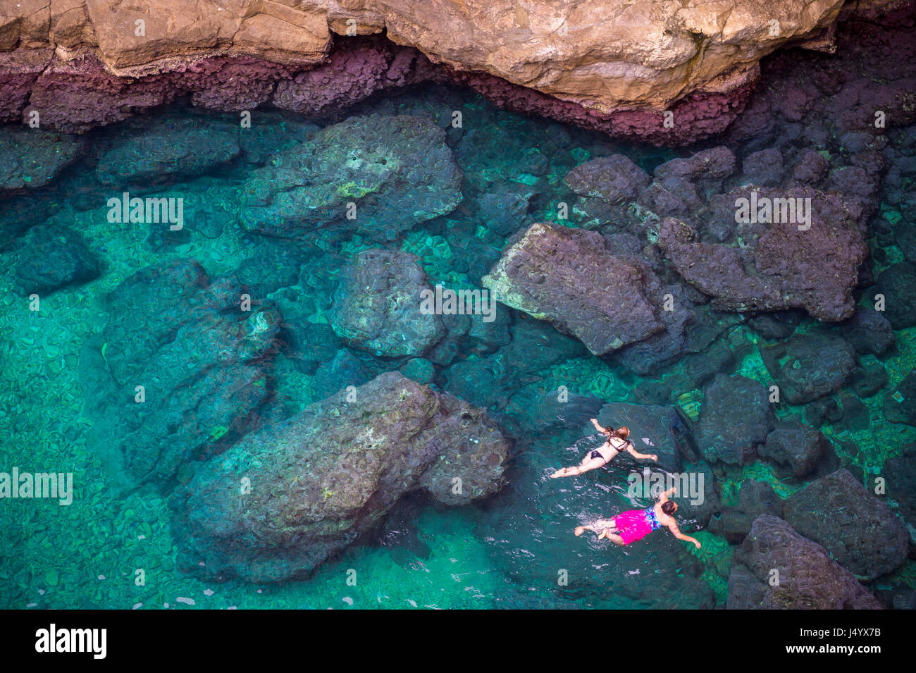 View from the rock cliffs of swimmers exploring the crystal clear Mediterranean waters of a cove off the coast of - Stock Image