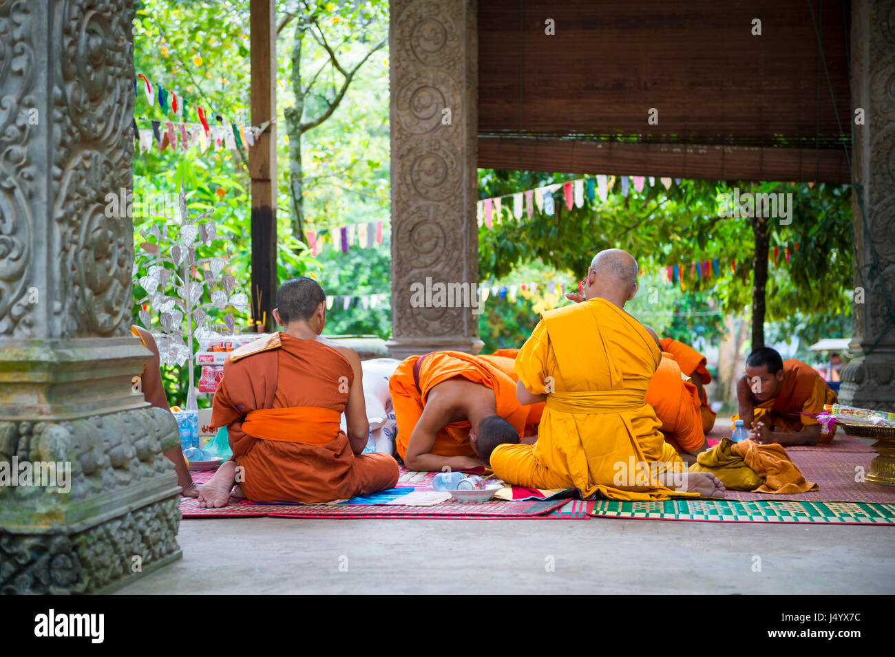 ANGKOR WAT, CAMBODIA - OCTOBER 30, 2014: Buddhist monks in saffron robes perform a ceremony at an outdoor temple - Stock Image