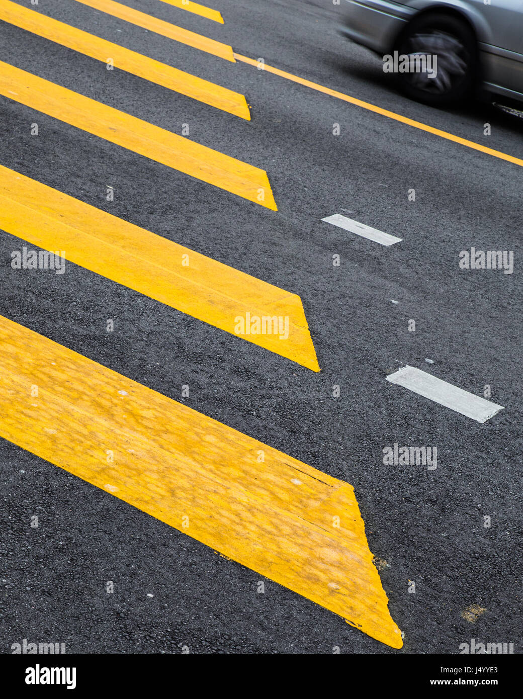 Yellow painted crosswalk road line markings with moving car in background - Stock Image