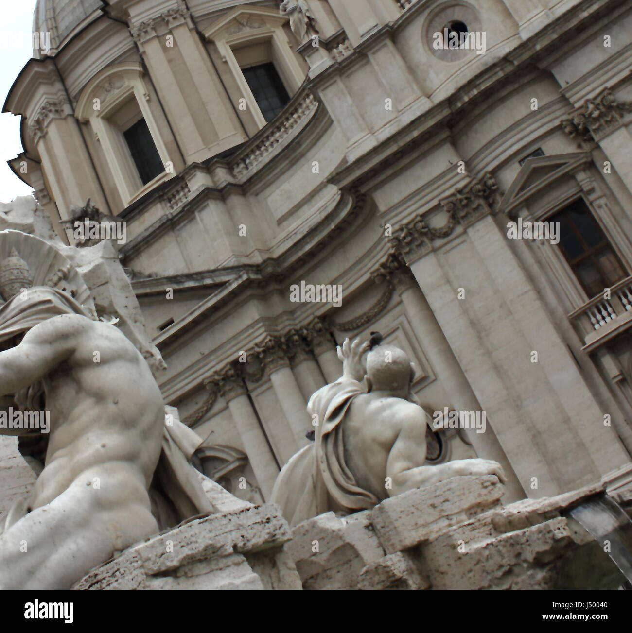 Close-up of the Fountain of the Four Rivers (Fontana dei Quattro Fiumi) with Sant'Agnese in Agone in the background, Stock Photo