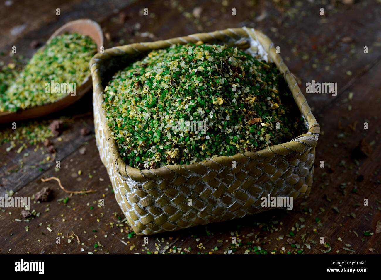 closeup of a square basket and a wooden spoon full of vegetable soup mix with semolina, on a rustic wooden table - Stock Image