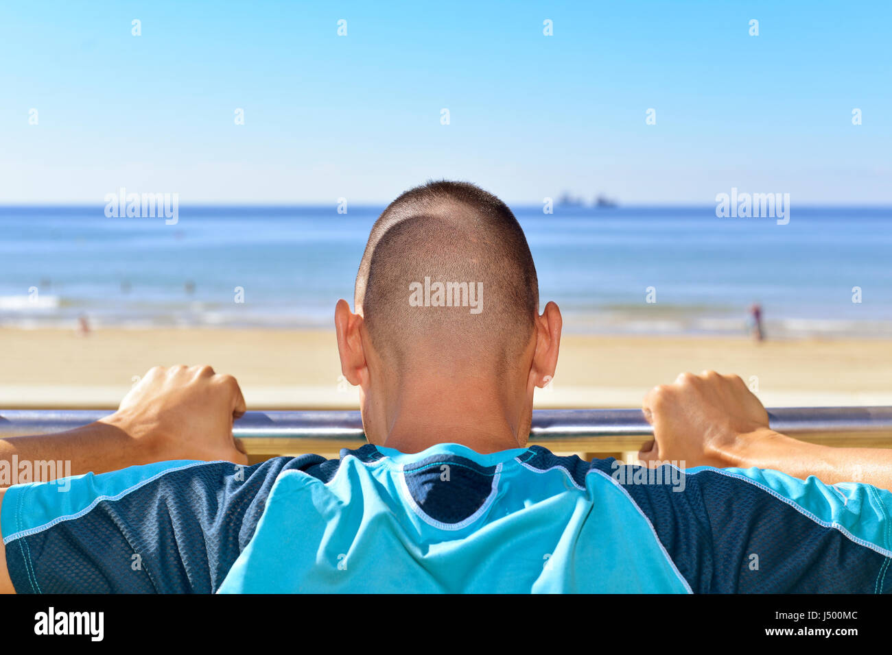 closeup of a young caucasian sportsman in sport clothes seen from behind doing incline push-ups in a metal bar outdoors, - Stock Image