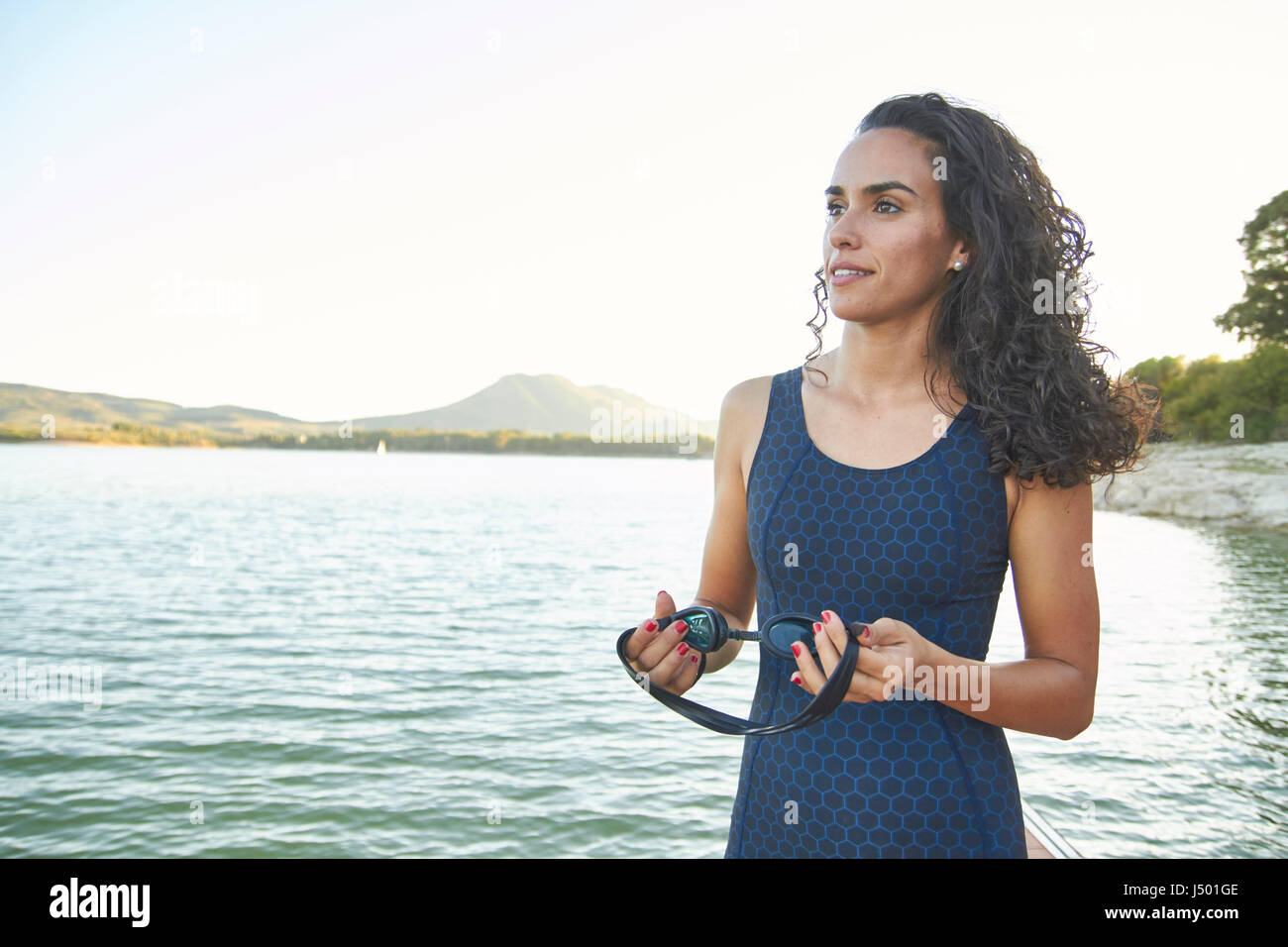 Female Triathlete at the edge of a lake - Stock Image