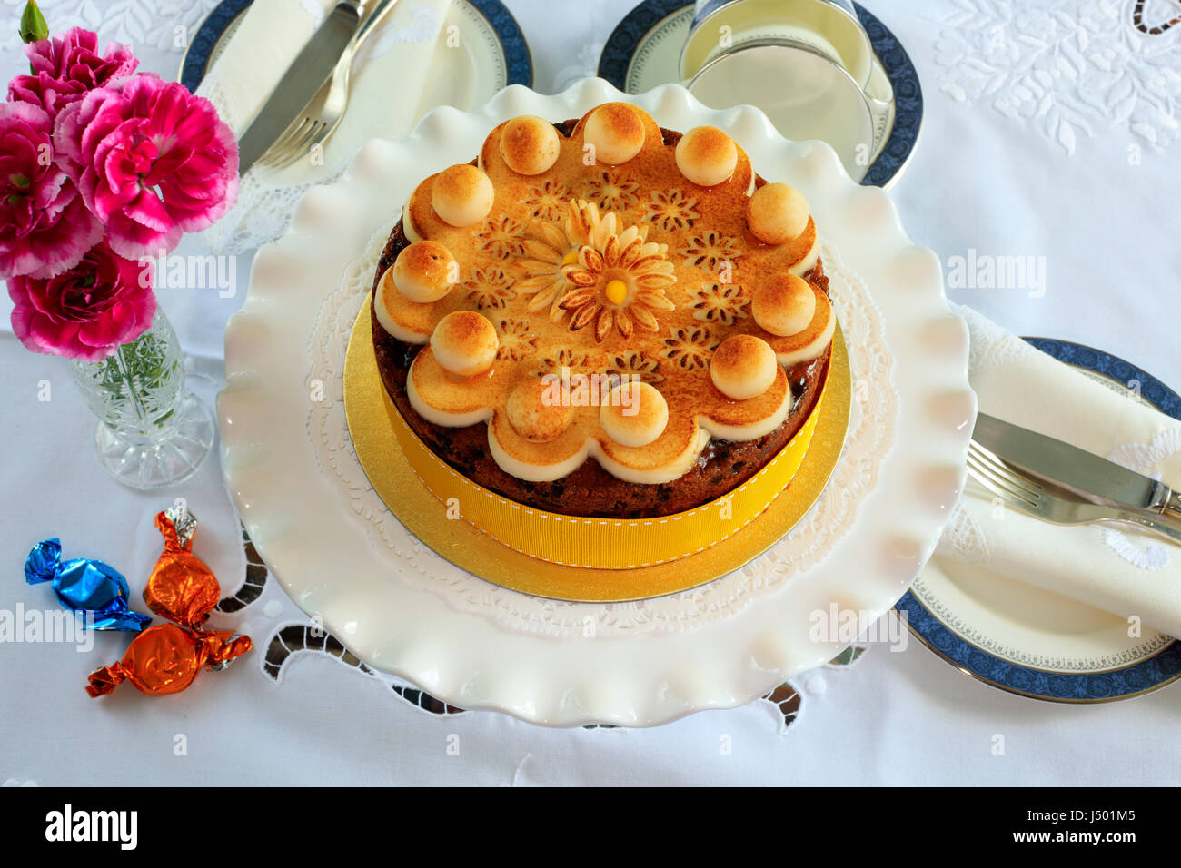 Simnel cake - traditional Easter fruit cake decorated with marzipan on a table set for tea. - Stock Image