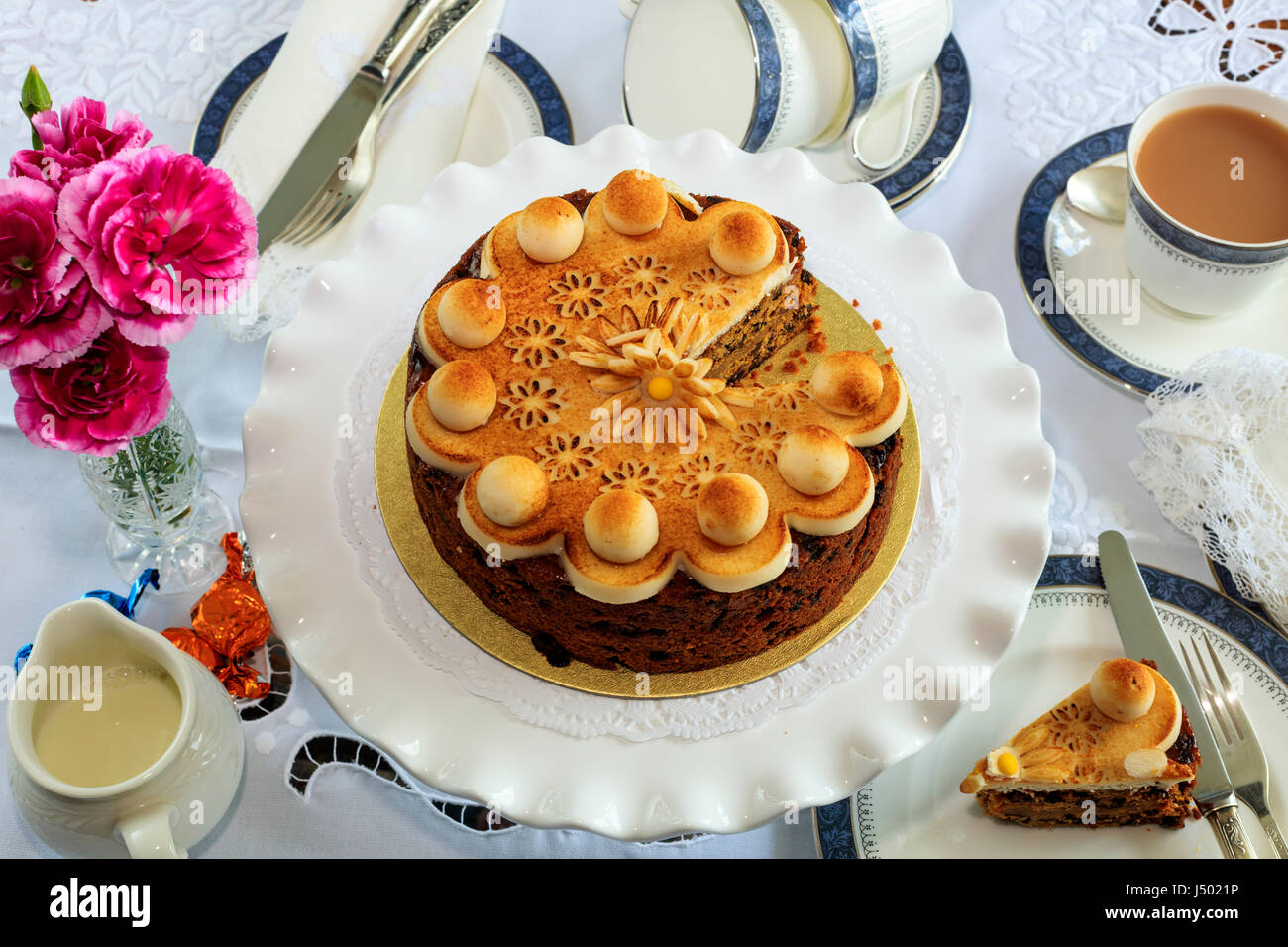 Simnel cake - traditional Easter fruit cake decorated with marzipan on a table set for tea. Stock Photo