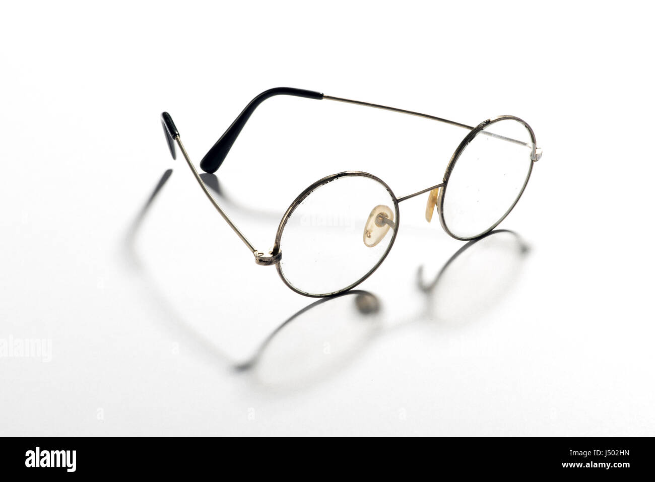 Pair of classic round vintage eyeglasses, glasses or spectacles with a thin wire frame displayed open throwing a - Stock Image