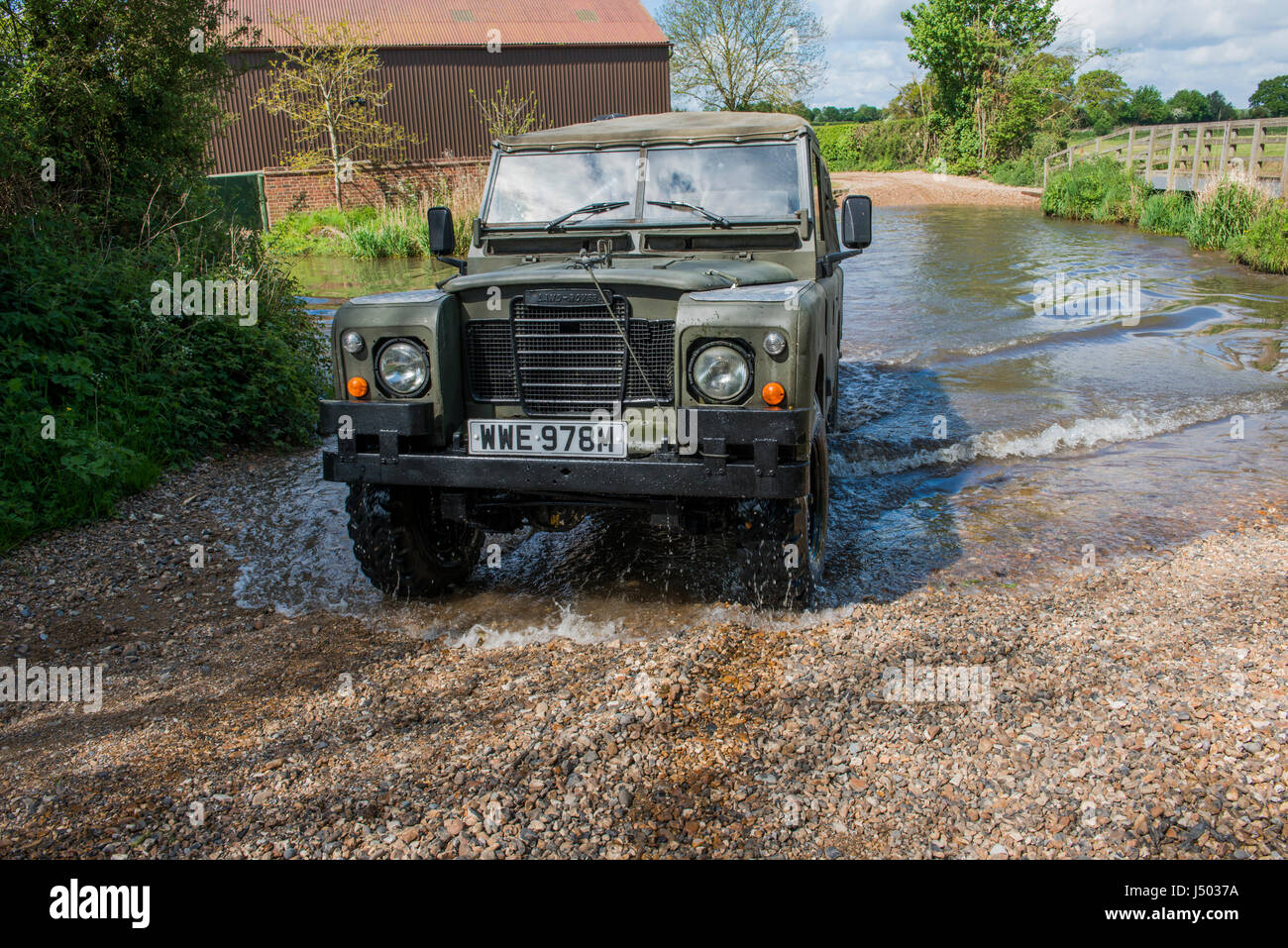 Model released image of a man driving a 1973 ex army Land Rover Series 3 Long Wheel Base into the river VER which Stock Photo