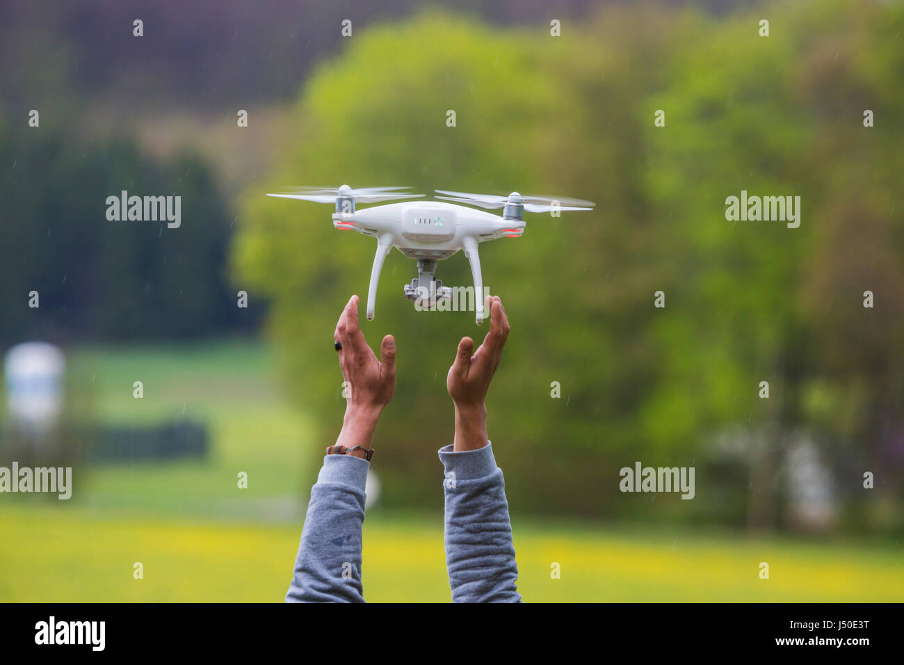 Drone of type DJI Phantom 4 at landing approach, is caught. - Stock Image