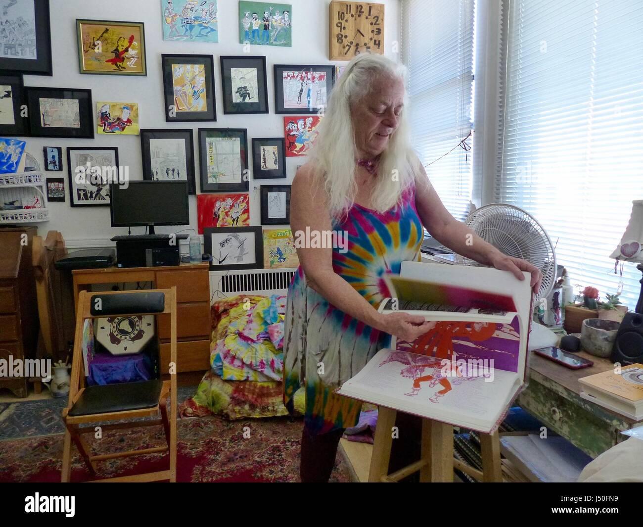 North Beach, San Francisco, USA. 1st May, 2017. Hippie artist Ann Cohen leafs through an art book in her apartment - Stock Image