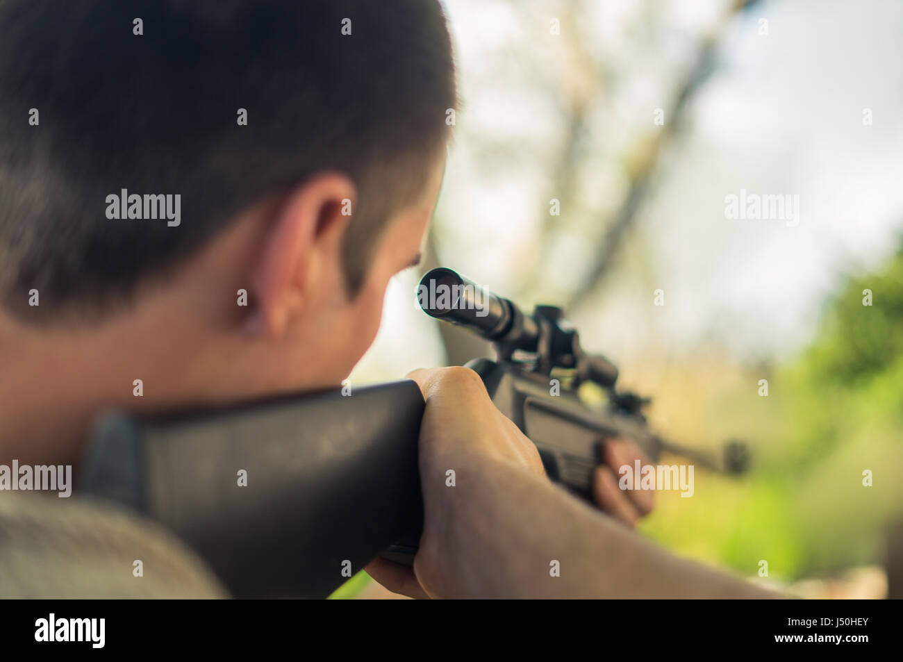 The man takes aim at the target with a sniper rifle. Selective Focus - Stock Image