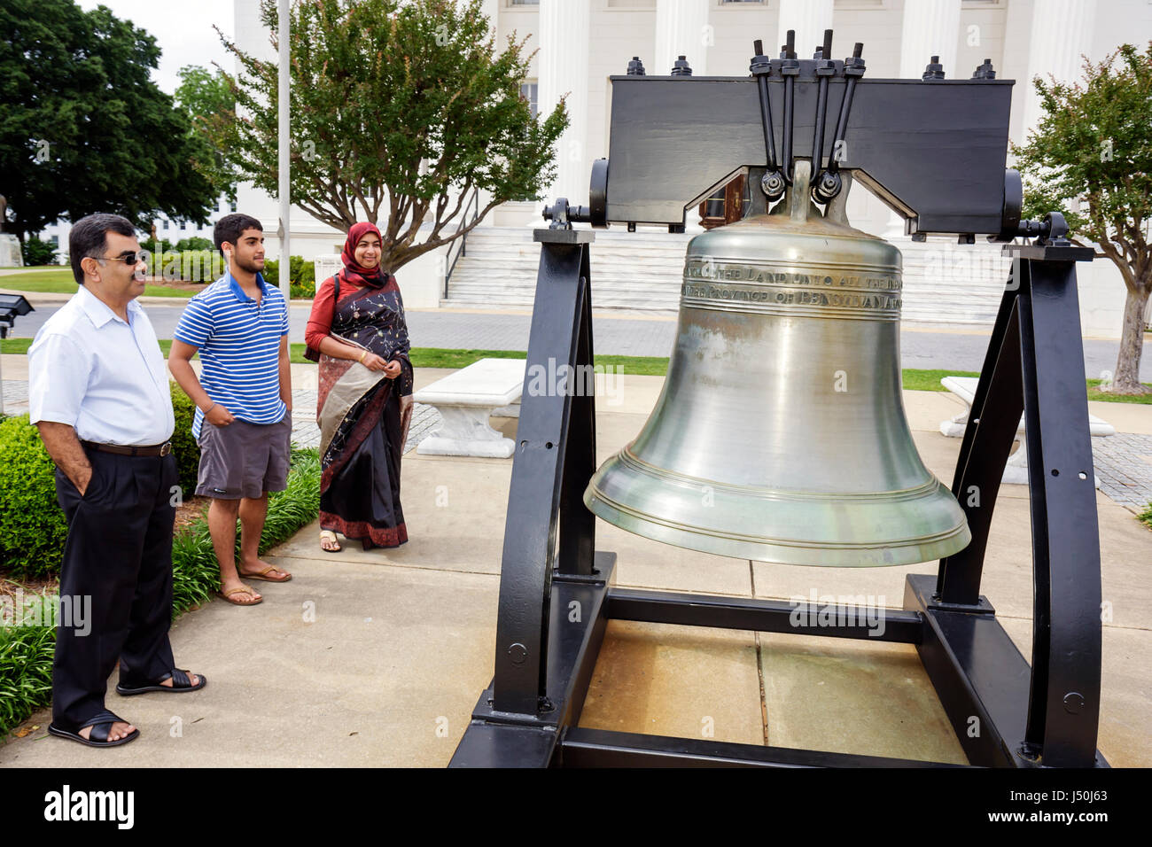 Montgomery Alabama State Capitol Building Liberty Bell replica Asian family Muslim man woman teen parents son government - Stock Image