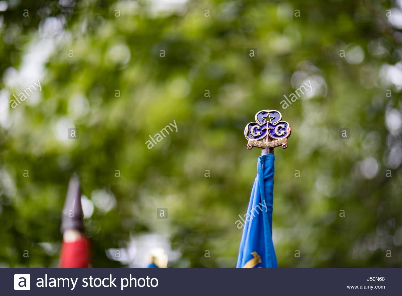 Girl Guiding emblem on top of a flag at a parade of members of the scouting and guiding movement to celebrate St - Stock Image