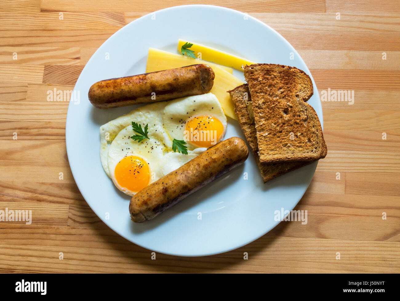 Two fried eggs sunny side up with sausage and cheddar cheese and whole wheat toast - Stock Image