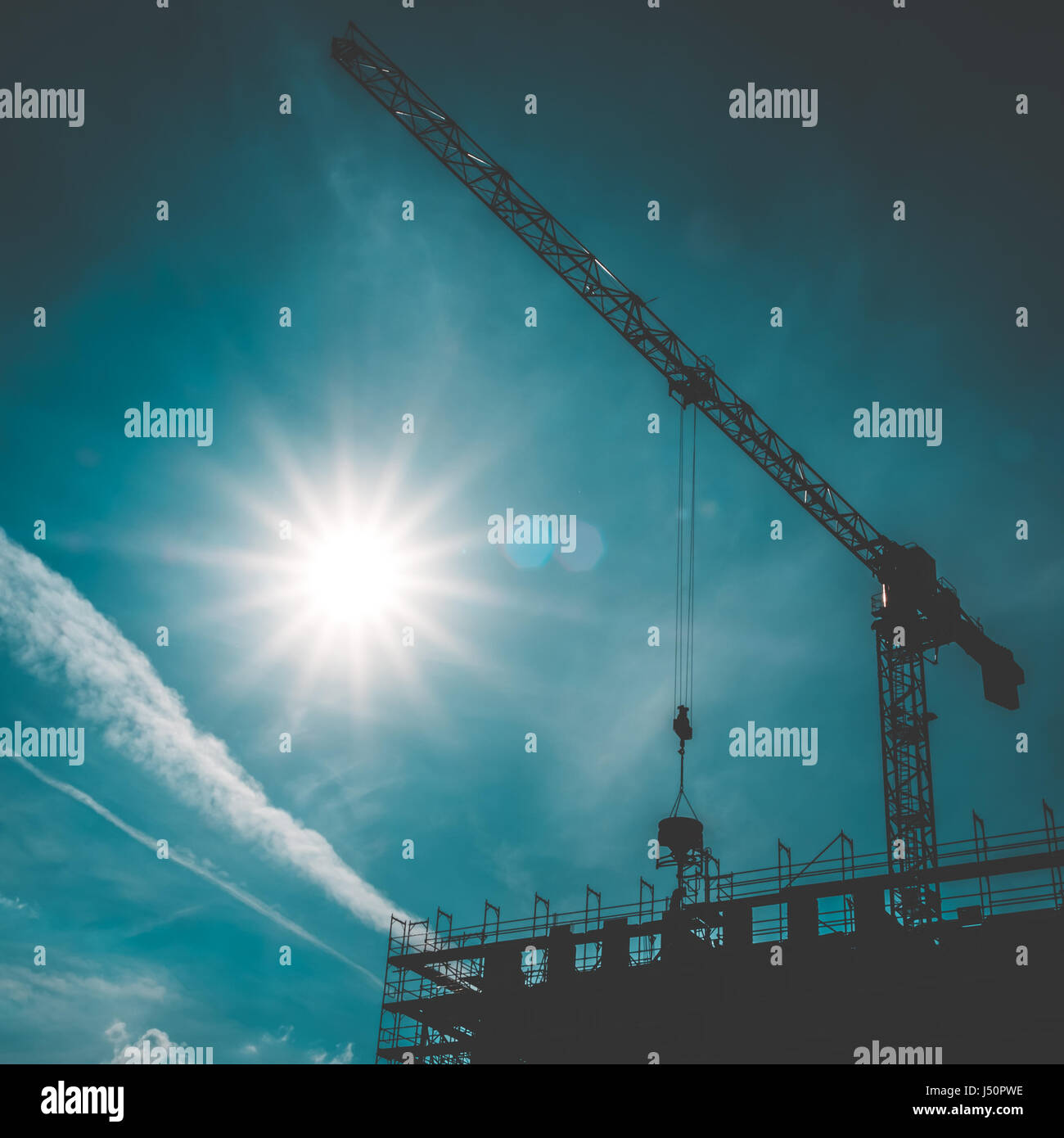 scaffolding and construction cranes silhouette on blue sky - Stock Image