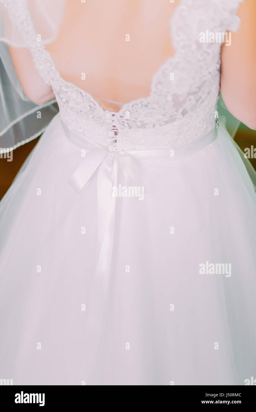 Close up of traditional white wedding dress at the back - Stock Image