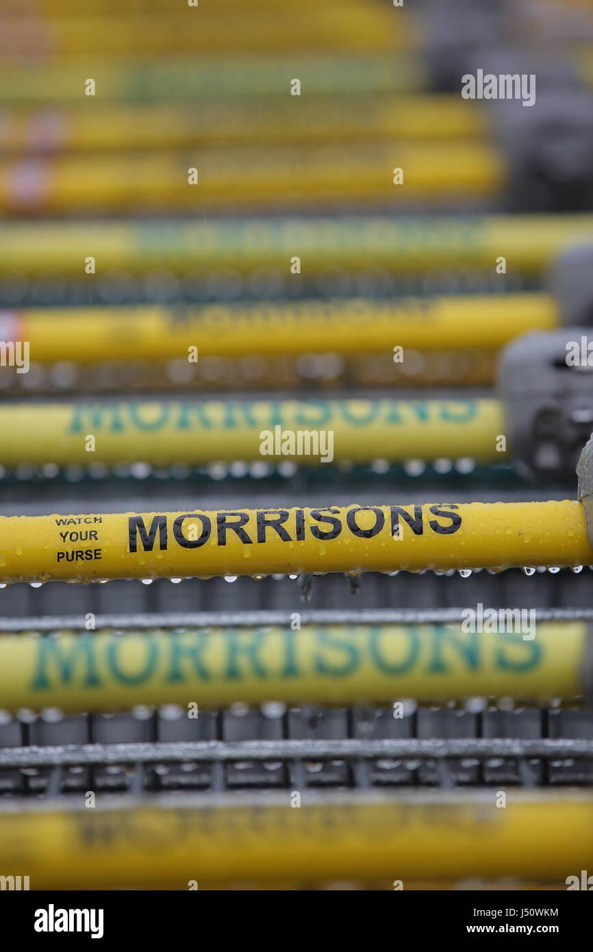Shopping trolleys' handlebars at a Morrisons super market - Stock Image