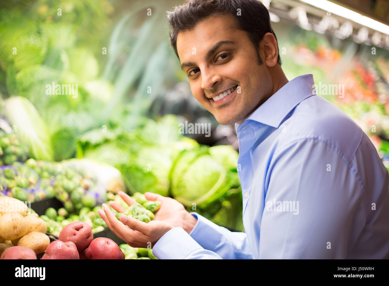 Closeup portrait, handsome young man in blue shirt picking up green brussel sprouts, choosing vegetables in grocery - Stock Image
