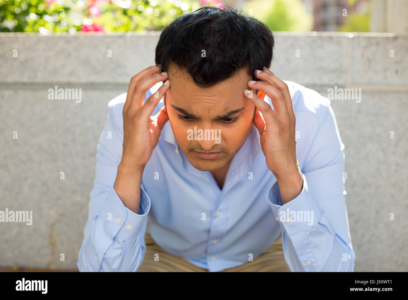 Closeup portrait, stressed young business man, hands on head with bad headache, isolated background of gray bench - Stock Image