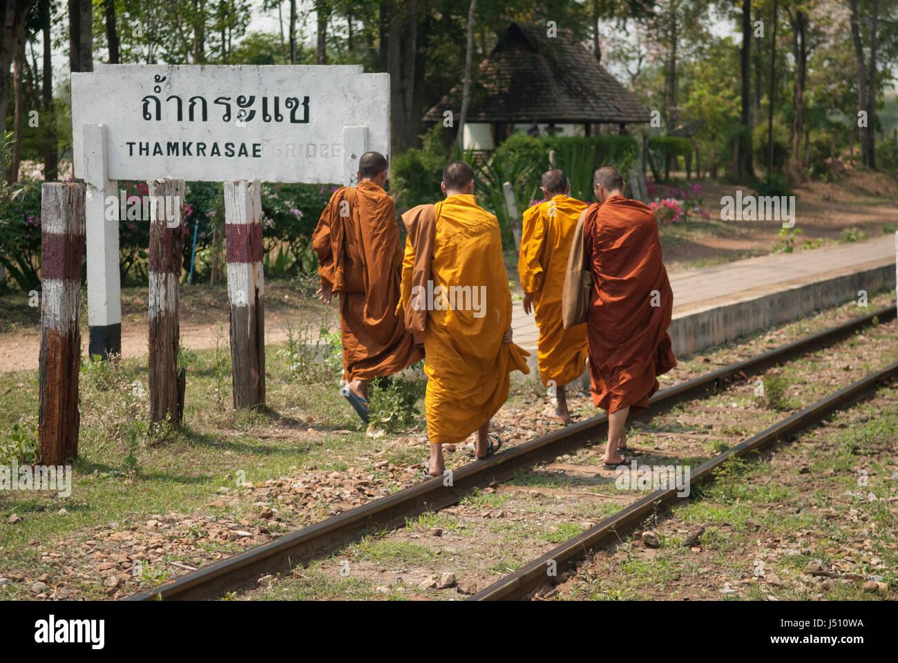 Four buddhist monks walking along the railway track at Thamkrasae Bridge station, Thailand - Stock Image