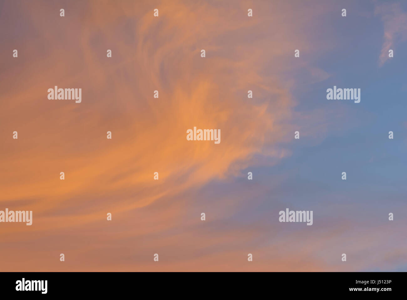 Whispy cloud formations in the sky tinted with the pastel colours of sunset. Suitable as a background. - Stock Image