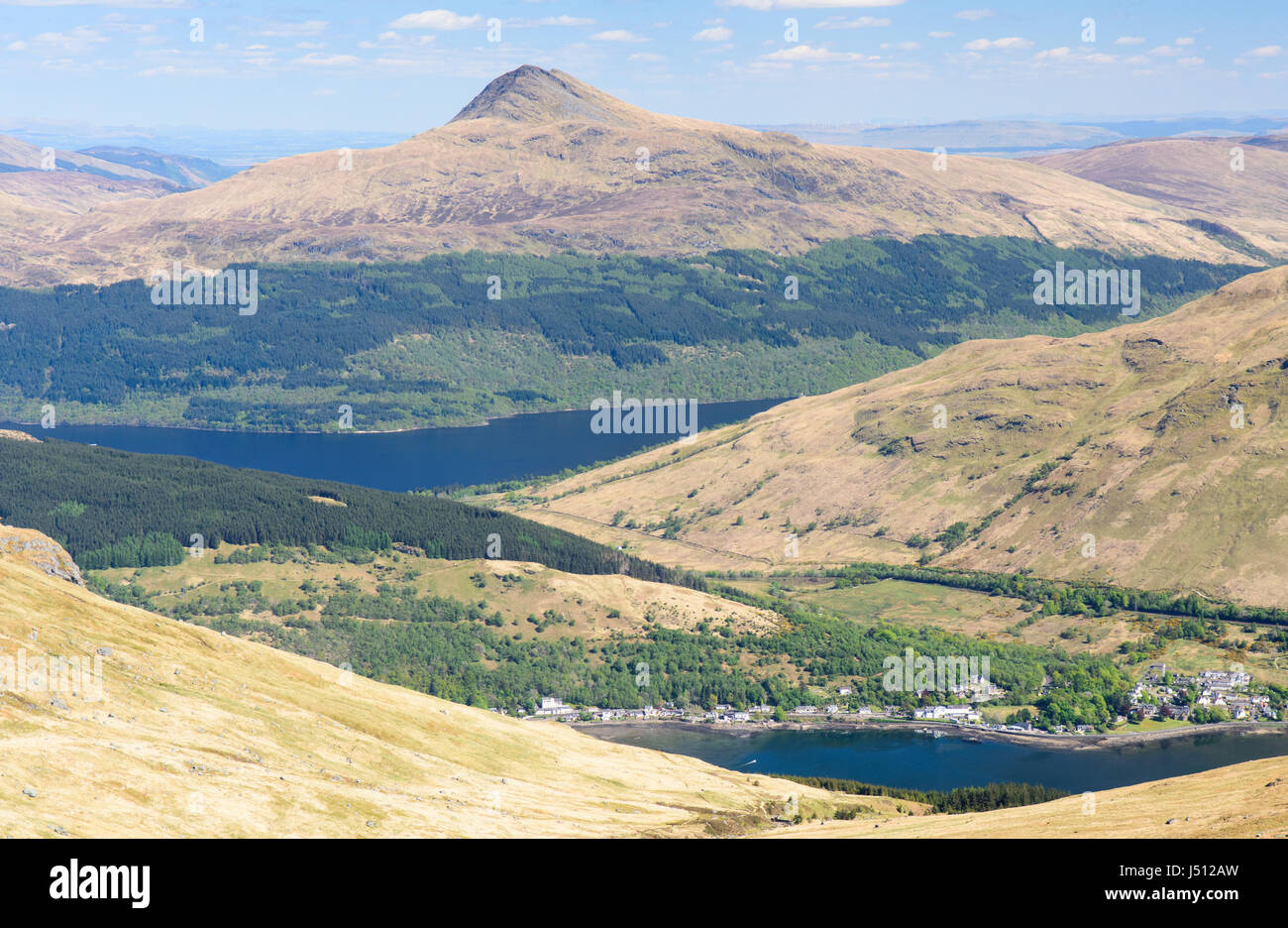 The forested slopes of Ben Lomond mountain rise from the shores of Loch Lomond lake, beyond Arrochar village, in - Stock Image