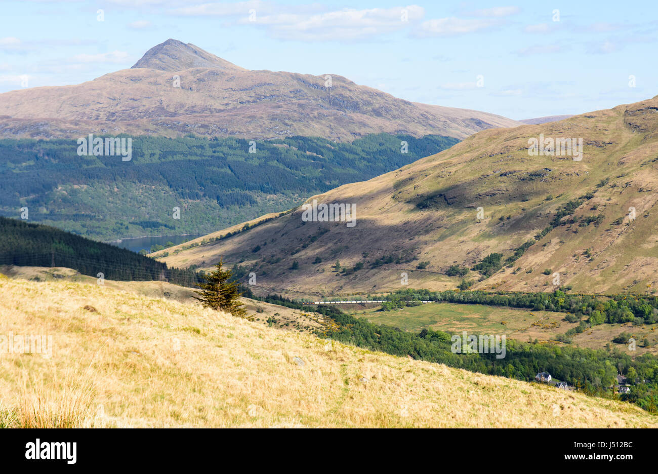 A freight train passes Arrochar on the West Highland Line railway, with Ben Lomond mountain rising behind. - Stock Image