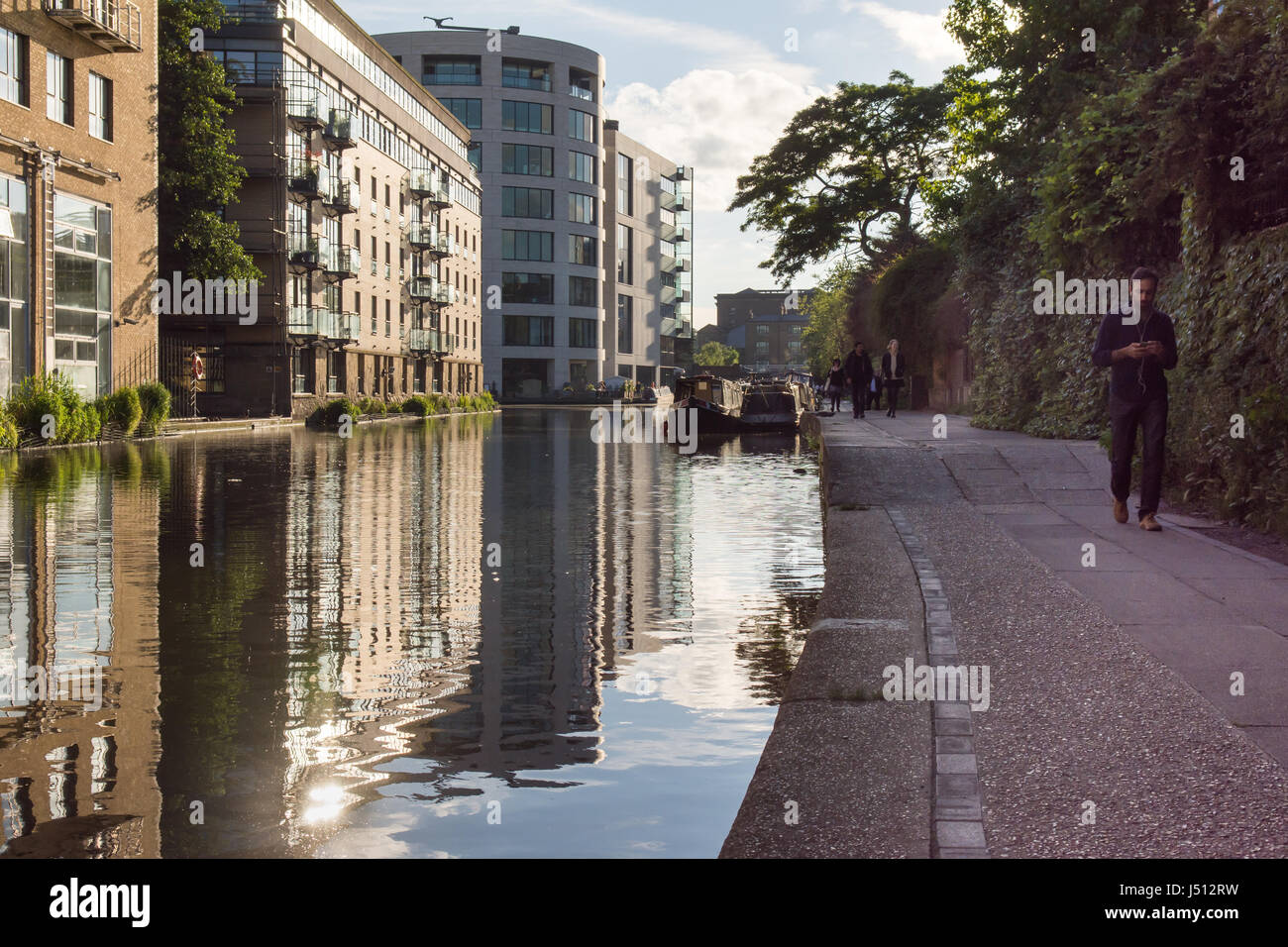 London, England - June 20, 2016: Pedestrians walk on the towpath of the Regent's Canal near King's Cross - Stock Image